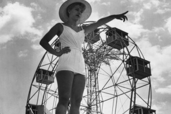 """A lifeguard at Steeplechase park, Coney Island stands with a whistle between her lips as she points to a transgressor in the pool below. In the background is a fairground big-wheel. July 1961.""(Getty)"